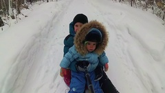 A happy children rides and smiling in snowtube on snow-covered roads Stock Footage