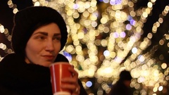 Happy young lady with cup of coffee against illuminated christmas tree Stock Footage