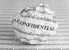 Crumpled paper ball with words Confidential Stock Photos