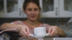 Lovely girl with light brown short hair, politely holding out a white cup of Stock Footage