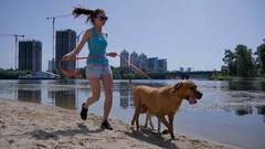 Cute girl running with her two dogs near the water Stock Footage