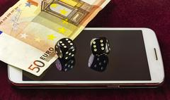 Smartphone, dice poker, and part of fifty euro banknotes Stock Photos