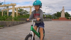 Toddler boy rides a balance bike in a park close to the sea in asia Stock Footage