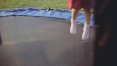 Children's legs running on the trampoline at summer sunset Stock Footage