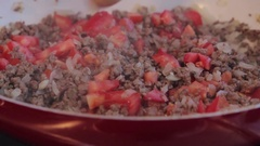 Chef mixing frying ground meat with sliced onions and tomatoes on ceramic pan.  Stock Footage