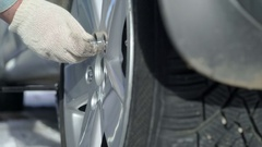 Man changing tire on his car in winter tightening the wheel nuts Stock Footage