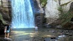 Kids playing at the base of a massive waterfall in North Carolina Stock Footage