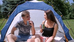 Lovely couple sits in tent and drinks tea in park Stock Footage