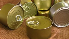 Closed metal tin cans on brown background Stock Footage