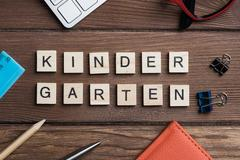 Office stuff and Kinder Garden phrase collected with letters on table Stock Photos