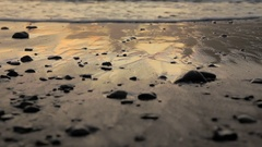 Waves gently lap over glistening sand and stones Stock Footage
