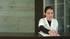 Spa manager filling in form and greeting customers at the reception desk Stock Footage