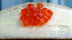 Red caviar runs down the butter on white bread Stock Footage