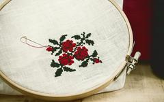 Hand embroidery cross-stitch flower ornament on a white fabric Stock Photos