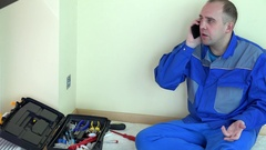 Tired electrician worker man talk modern mobile phone Stock Footage