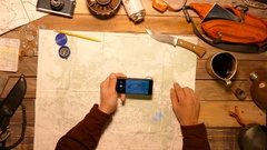 Traveler, tourist making photo of hiker map using smartphone. Top view. Stock Footage