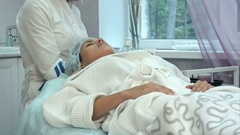 Masseuse putting oil on young female face before starting facial massage Stock Footage