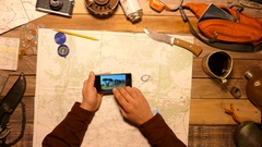 Traveler, tourist watching photos of his hike, using smartphone. Top view. Stock Footage
