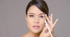 Pretty young brunette woman applying makeup Stock Footage