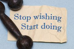 Stop wishing, start doing! Motivational phrase on a sheet of paper with a d.. Stock Photos