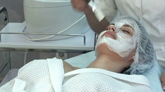 Spa woman appllying clay facial mask with a brush Stock Footage