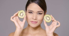 Vivacious young woman with a halved kiwifruit Stock Footage
