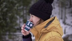 Young woman in black bobble hat walks near the trees in snow drinking hot Stock Footage