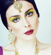 Young pretty caucasian woman like indian in ethnic jewelry close up on white Kuvituskuvat