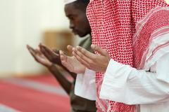 Two religious muslim man praying together inside the mosque Kuvituskuvat