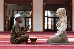 Black Muslim man and woman praying in mosque Kuvituskuvat