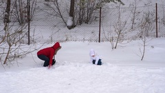 Mother and daughter throw up soft, fresh snow. Stock Footage