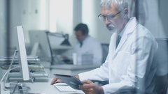 Senior Medical Practitioner Sitting Before Personal Computer Uses Tablet Compute Stock Footage