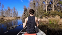 Teen paddling through the Okefenokee swamp on the Georgia, Florida border Stock Footage