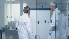 Two Specialist Doctors Discussing Health Issues and Medical Drug Trial Results  Stock Footage