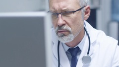 Close-up Portrait of a White Haired Doctor Working on Personal Computer.  Stock Footage