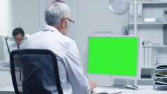 Senior Medical Doctor Working on a Mockup Green Screen Personal Computer.  Stock Footage