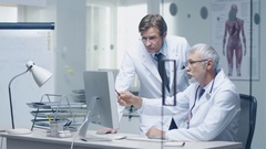 Senior Doctor and His Assistant Discuss Patient's Log on Personal Computer. Stock Footage