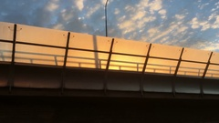 Car silhouettes on noise barrier on motorway flyover in Stockholm at dusk, Stock Footage