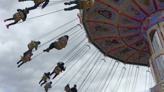 People riding a chain carousel Stock Footage