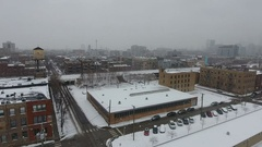 Aerial View Snow covered city buildings water tower snow building parking lot Stock Footage
