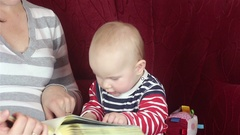 Young mother reading a book with baby Arkistovideo