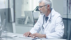 Close-up of a Senior Doctor and His Assistant Working at Desktop Computers.  Stock Footage