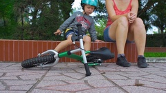 Toddler boy and his mom sit in a pakr with a balance bike in front. Slow motion Stock Footage