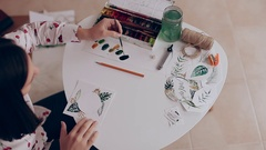 Girl drawing with brush and watercolor on paper. Handmade holiday ornaments Stock Footage