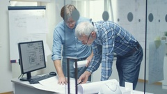 Two Senior Engineers Work with Schemes and Plans Standing over Working Table.  Stock Footage
