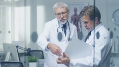 Two Specialist Doctors Discussing Patient's Log. Both are Senior and Experienced Stock Footage
