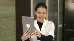 Happy beauty salon manager taking selfies with her tablet at the reception desk Stock Footage