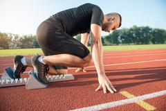 Male athlete on starting position at athletics running track Stock Photos