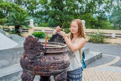 Young woman Traveler praying in polite action with incense sticks at buddhi.. Stock Photos