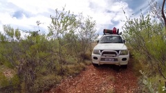 4x4 Vehicle driving over red earth through Australian outback bush Stock Footage